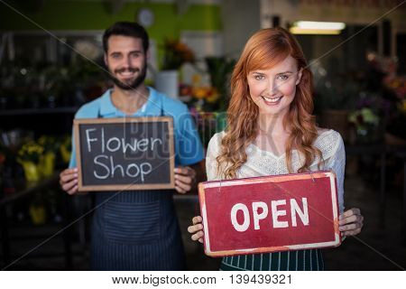 Woman holding open signboard and man holding slate with flower shop sign in the flower shop