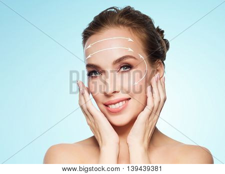 beauty, plastic surgery, facelift, people and rejuvenation concept - beautiful young woman touching her face with lifting arrows over blue background