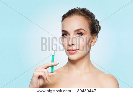 health, people, cosmetology, plastic surgery and beauty concept - beautiful young woman holding syringe with injection over blue background