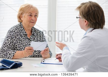 Female doctor explaining diagnosis to her senior patient