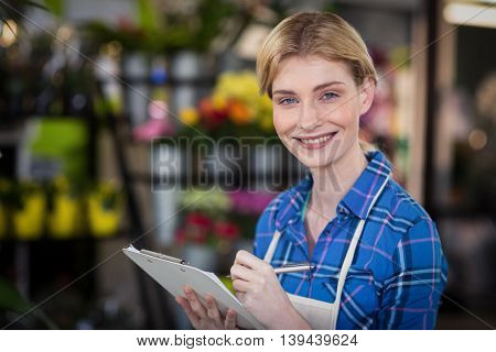 Portrait of female florist writing on clipboard in the flower shop