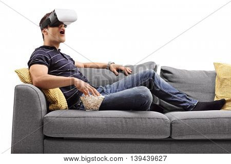 Amazed young man looking in VR goggles and eating popcorn seated on a sofa isolated on white background