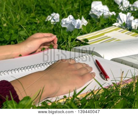 girl in a burgundy sweater is put her hands on the book, which lies on the green grass, notebook empty, a creative crisis, is located next to the red pen and book