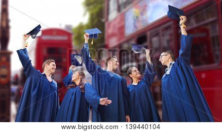 education, graduation and people concept - group of happy smiling students in gowns waving mortarboards over london city street background