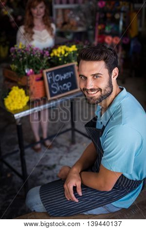 Portrait of male florist sitting and smiling in the flower shop
