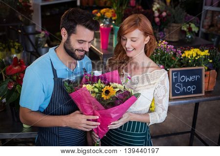 Couple holding flower bouquet in the flower shop