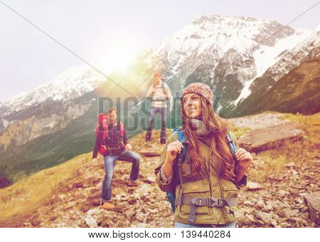 adventure, travel, tourism, hike and people concept - group of smiling friends with backpacks walking down downhill over alpine mountains and hills background