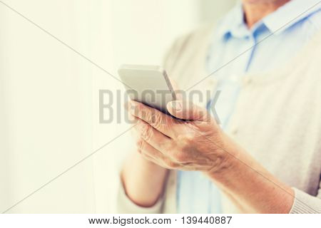 technology, communication age and people concept - close up of senior woman hands with smartphone texting message at home