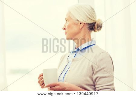 age, loneliness and people concept - lonely senior woman with cup of tea or coffee looking through window at home