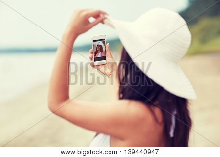 travel, summer, technology and people concept - sexy young woman taking selfie with smartphone on beach