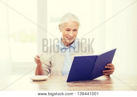 age, leisure and people concept - happy smiling senior woman drinking coffee and reading book at home