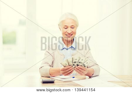 business, savings, annuity insurance, age and people concept - happy senior woman with calculator and bills counting dollar money at home