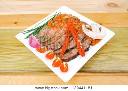 grilled beef slice on plate over wooden table