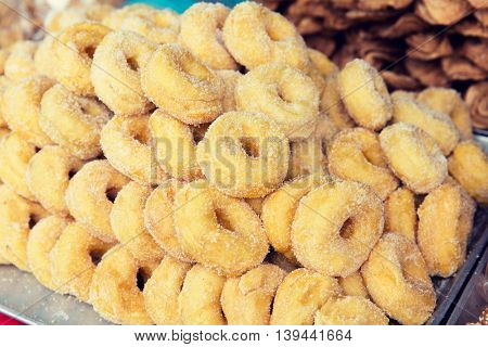 cooking, asian kitchen, sale and food concept - sugared donuts at asian street market