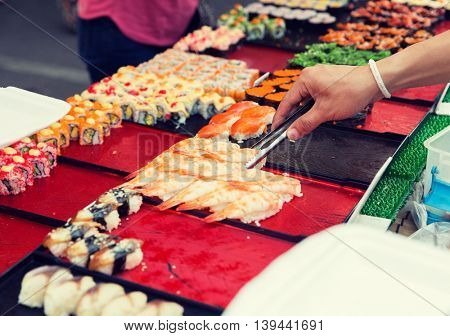 cooking, asian kitchen, sale and food concept - close up of hand with tongs taking sushi at street market