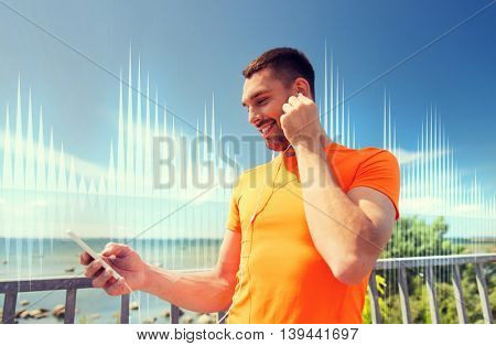 fitness, sport, people, technology and healthy lifestyle concept - smiling young man with smartphone and earphones listening to music at summer seaside over sound wave or signal diagram