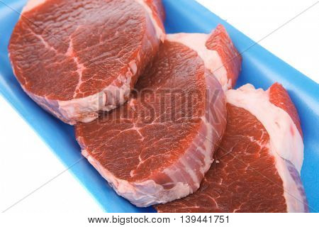 raw meat : fresh beef pork big tenderloin strip on blue tray isolated over white background
