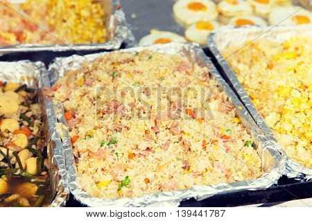 cooking, asian kitchen, sale and food concept - wok or pilaf dish at street market