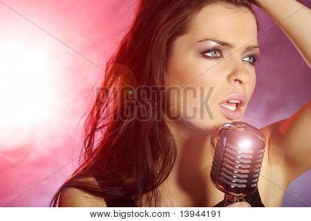 Music star.Sexy woman singing in retro mic