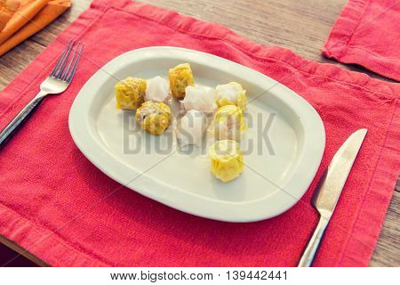 cooking, asian kitchen and food concept - plate of spring rolls with rice, fork and knife on wooden table at restaurant