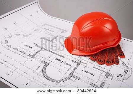 Construction helmet and protective gloves, construction of the building layout, building drawing on paper, protective clothing