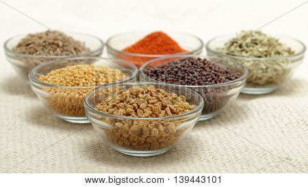 Different types of Indian spices in glass bowl, focus on Fenugreek seeds on jute mat background. Front view.