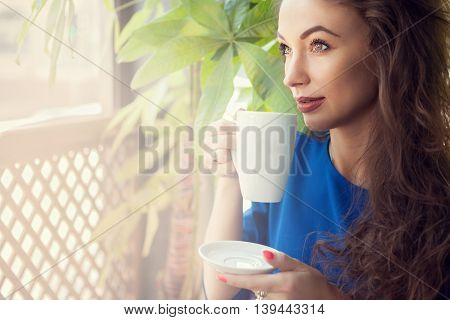 Woman Drinking Coffee At Terrace