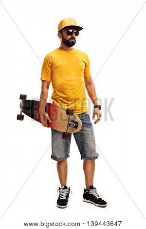 Full length portrait of a cool man in a yellow shirt and cap holding a longboard isolated on white background