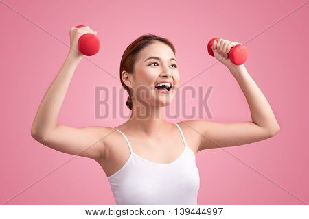 Woman Lifting Weights. Fitness woman lifting weights smiling happy on pink background.