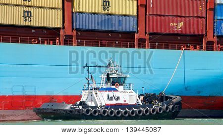 Oakland CA - July 19 2016: Tugboat PATRICIA ANN assisting GERDA MARSK maneuver into the Port of Oakland. Tugs move vessels that should not move themselves such as ships in a crowded harbor.