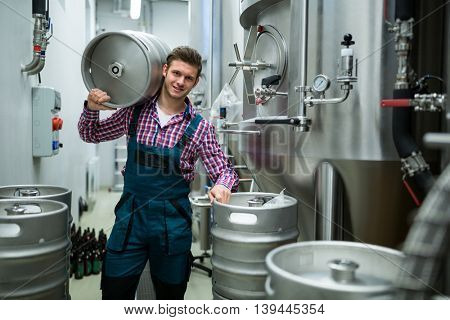Portrait of brewers carrying keg on shoulder at brewery factory