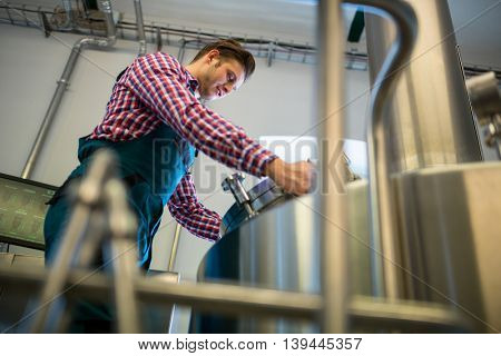 Attentive maintenance worker working at brewery