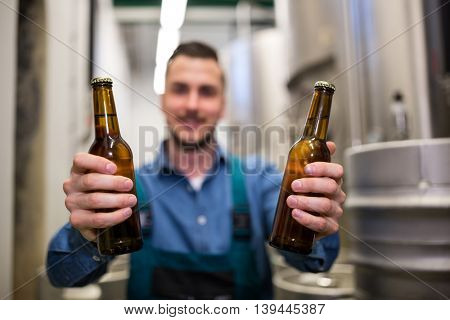 Brewer holding two beer bottle at brewery