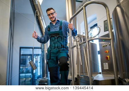 Portrait of happy brewer holding working equipment at brewery