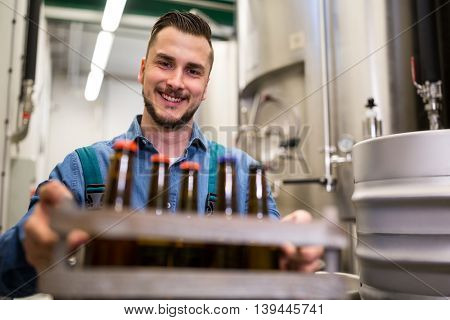 Portrait of happy brewer holding beer bottles in crate at brewery