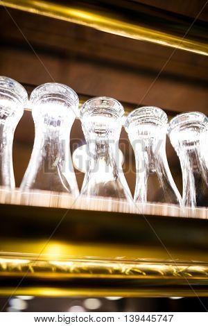 Glasses arranged on the bar shelf at restaurant