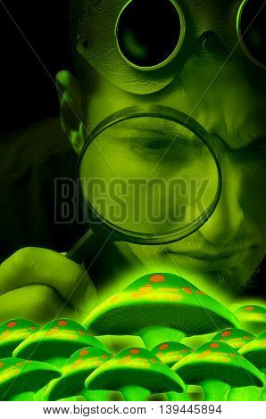 Man looking through magnifying glass at glowing mushrooms