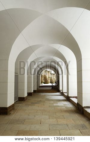 The historical building.Arches inside of the building painted white.