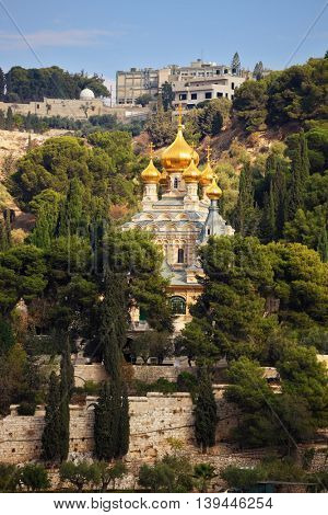 Orthodox Church of Mary Magdalene in Jerusalem. Golden domes topped with a gold cross in the green park