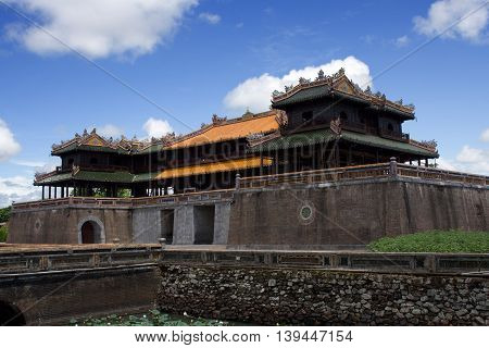 Side view on the Hue Imperial Palace in the Imperial City Hue Central Vietnam. The palace is surrounded with water dungeons with pond lilies. Summer photo with blue sky with few clouds.