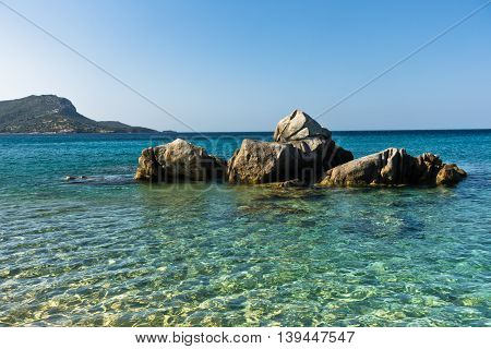 Sea rocks and turquoise water near sandy beach at morning, west coast of peninsula Sithonia, Chalkidiki, Greece