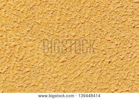 Plastered concrete surface with an uneven rough texture painted in yellow color
