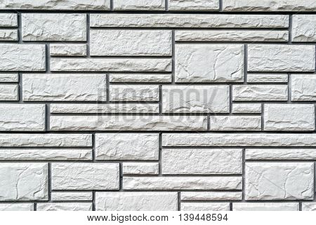Surface of the wall decorated with rectangular panels with horizontal artificial stone texture