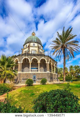 The basilica is surrounded by a gallery with columns. Church Sermon on the Mount - Mount of Beatitudes. Subtle shade of palms and cypresses