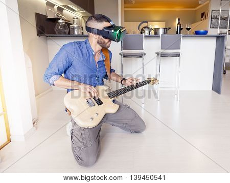 Young Adult Playing Guitar At Home Using Viewer For Virtual Reality