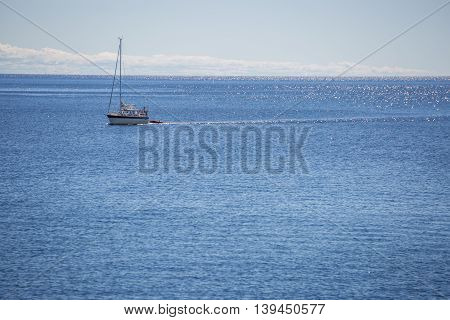 Sailboat on Ocean with a partly cloudy sky.