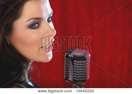 Rock star.Sexy Girl singing in retro mic