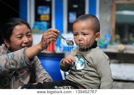 Khumbu Region, Nepal - Oct 20, 2012: Nepali woman feeding her son their house yard on a cold autumn season