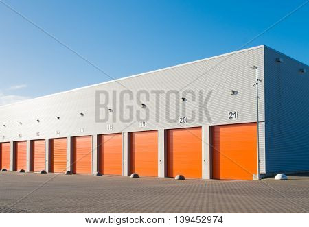 ENSCHEDE, NETHERLANDS - NOVEMBER 28, 2015: Exterior of a commercial warehouse with orange roller doors