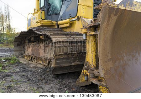 close-up of a yellow excavator in the mud